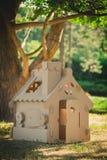 Stuk speelgoed huis van golfkarton in het stadspark dat wordt gemaakt Stock Fotografie