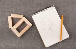 Stuk speelgoed huis van houten blokken, blocnote en pencilon grijze backg wordt gemaakt die Royalty-vrije Stock Foto