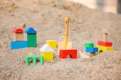 Stuk speelgoed huis van houten blokken in zandbak wordt gemaakt die Stock Afbeeldingen