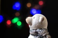Stuk speelgoed ijsbeer op een zwarte achtergrond met lichten van Kerstmisslingers royalty-vrije stock foto
