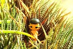 stuk speelgoed jongen met gele zonnebril in de groene cactusstruiken royalty-vrije stock foto