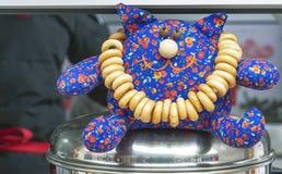 Stuk speelgoed kat met ongezuurde broodjes op een metaalschotel stock foto's