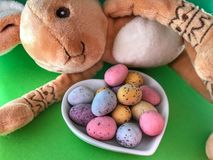 Stuk speelgoed konijn die naast een schotel van paaseieren liggen stock foto