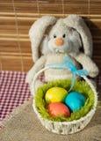 Stuk speelgoed konijn met een mand van paaseieren stock afbeelding
