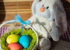Stuk speelgoed konijn met een mand van paaseieren stock foto's