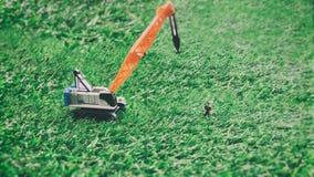 stuk speelgoed kraan en de miniatuur van de mensenarbeider op groen grasgebied Constru Stock Foto's