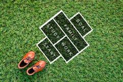 Stuk speelgoed leerschoen op de textuur van het achtergrond grasgebied het levensconcept Royalty-vrije Stock Foto