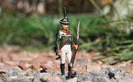Stuk speelgoed militair onder de rotsen Stock Foto