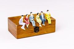 Stuk speelgoed modellen van mensen die op de houten doos zitten Royalty-vrije Stock Foto's