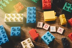 Stuk speelgoed plastic bakstenen op houten lijst met het woordidee van alfabettegels stock afbeeldingen