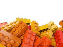 Stuk speelgoed plastic bakstenenachtergrond in warme kleuren Stock Afbeeldingen