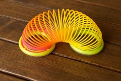 Stuk speelgoed plastic regenboog op een houten lijst Multi-colored spiraal voor stock foto