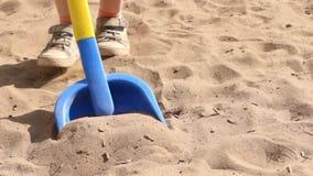 Stuk speelgoed schop en voeten van weinig jongen die op zand bij de zomer gaan stock video