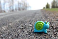 Stuk speelgoed slak op de weg Stock Foto's