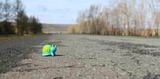 Stuk speelgoed slak op de weg Stock Afbeeldingen