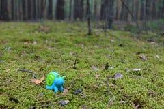 Stuk speelgoed slak op het mos Stock Afbeelding