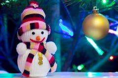 Stuk speelgoed sneeuwman op de achtergrond van een feestelijke Nieuwjaar` s achtergrond Stock Foto's