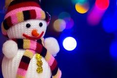 Stuk speelgoed sneeuwman op de achtergrond van een feestelijke Nieuwjaar` s achtergrond Stock Fotografie