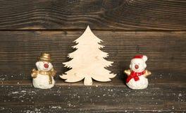 Stuk speelgoed sneeuwmannen en houten Kerstboom op een donkere houten backgroun Stock Afbeeldingen