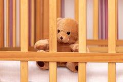Stuk speelgoed teddybeer in een babywieg stock afbeeldingen