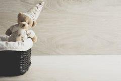 Stuk speelgoed teddybeer in een rieten mand op de lijst Stock Foto