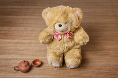 Stuk speelgoed teddybeer en theeketel en kop op houten achtergrond Stock Foto