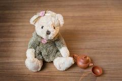 Stuk speelgoed teddybeer en theeketel en kop op houten achtergrond Stock Foto's