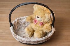 Stuk speelgoed teddybeer in mand op houten bureau wordt geïsoleerd dat Stock Fotografie