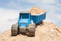 Stuk speelgoed tractor met zand Stock Foto