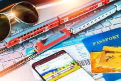 Stuk speelgoed trein, kaartjes, paspoort en betaalpas op laptop of notitieboekje Stock Foto's