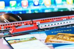 Stuk speelgoed trein, kaartjes, paspoort en betaalpas op laptop of notitieboekje Royalty-vrije Stock Afbeeldingen