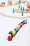 Stuk speelgoed trein met auto's en houten stuk speelgoed spoorweg met sparren royalty-vrije stock foto