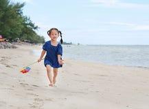 Stuk speelgoed van de de greep het kleurrijke windmolen van het babymeisje en het lopen op het strand in de avond royalty-vrije stock foto's
