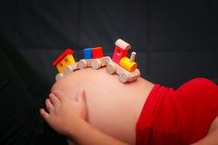 Stuk speelgoed van de jonge geitjes het houten trein op een zwangere buik Conc babyverwachting stock foto