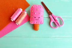 Stuk speelgoed van het hand het leuke gevoelde roomijs Roze wolroomijs met kralenversieringsborduurwerk De draad, naald, schaar,  Royalty-vrije Stock Foto