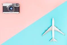 Stuk speelgoed vliegtuig en camera op roze en blauwe achtergrond royalty-vrije stock afbeeldingen