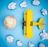 Stuk speelgoed vliegtuig op document de reis van de wolkenhemel Stock Foto's