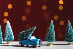 Stuk speelgoed vrachtwagen die een Kerstboom dragen stock foto