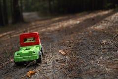 Stuk speelgoed vrachtwagen op een schaduwrijke bosweg Stock Foto's
