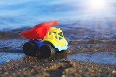 Stuk speelgoed vrachtwagen op het gouden zandige strand Rode, blauwe en gele auto op t stock afbeeldingen