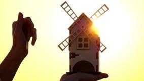 Stuk speelgoed windmolen in de hand van een jong meisje bij zonsondergang De molen roteert in een trager tempo Het concept het oo stock videobeelden