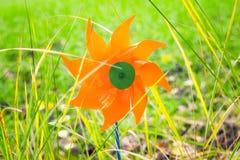 Stuk speelgoed windmolen in het gras Stock Foto
