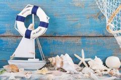Stuk speelgoed zeilboot en reddingsboei met zeeschelpen en zeester een hout Stock Fotografie