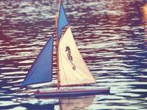 Stuk speelgoed zeilboot op een vijver royalty-vrije stock afbeeldingen