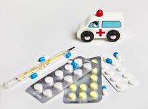 Stuk speelgoed ziekenwagen naast de medicijn en kwikthermometer stock foto