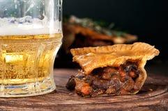 Stuk van Australische vleespastei met een glas licht bier Royalty-vrije Stock Afbeelding