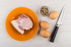 Stuk van borststuk, specerij, kippeneieren en mes op lijst royalty-vrije stock foto's