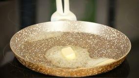 Stuk van boter die op een pan smelten stock video