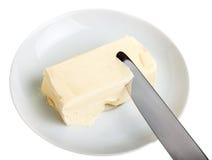 Stuk van boter op een schotel en een mes Royalty-vrije Stock Afbeelding