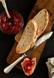 Stuk van brood met boter en jam op de houten raad wordt gesmeerd die Royalty-vrije Stock Foto